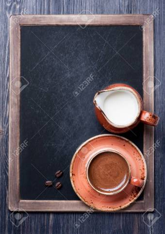 Cup of coffee with milk on vintage chalkboard
