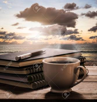 Hot coffee with notebooks and pen on wooden table with view of t